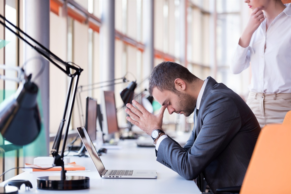 frustrated young business man working on laptop computer at office.jpeg